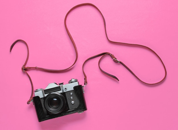 Vintage retro-filmkamera im lederbezug mit riemen auf rosa