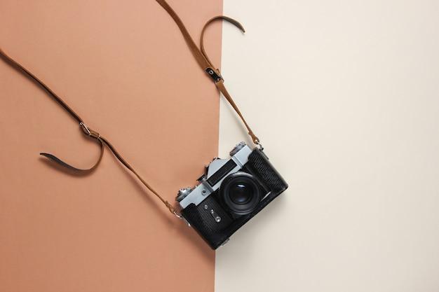 Vintage retro-stil filmkamera in lederbezug mit riemen auf braun.