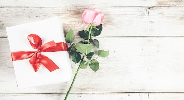 Vintage rosenblumen und geschenkbox mit schleifenband auf leuchttisch