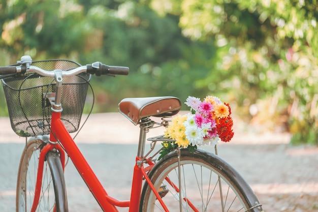 Vintage rotes fahrrad mit blumenstrauß.