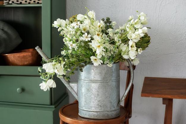 Vintage rustikales gartenwerkzeug schöner blumenstrauß blumen gänseblümchen in gießkanne auf holzstuhl wooden