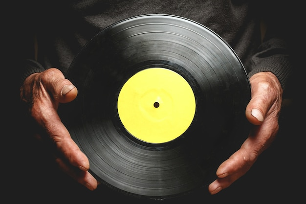 Vintage schallplatte in den händen eines älteren mannes