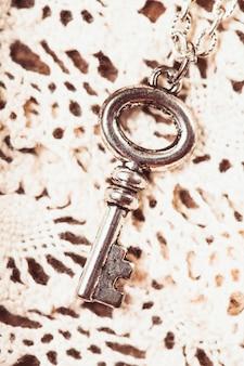 Vintage-schlüssel auf der weißen gealterten spitze