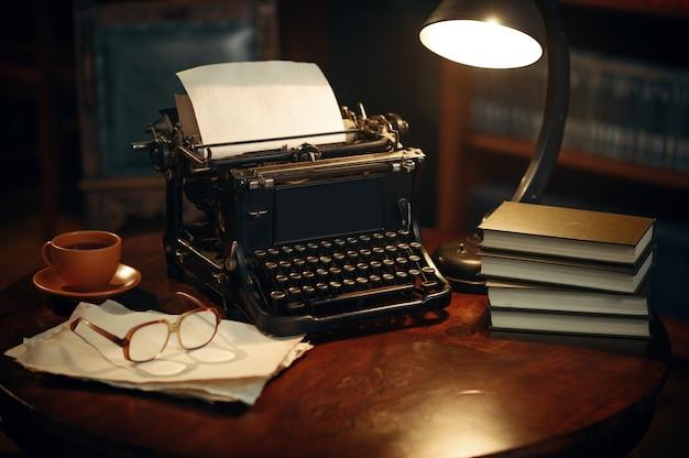 Vintage schreibmaschine auf holztisch im home office, niemand. schriftstellerarbeitsplatz im retro-stil, tasse kaffee und gläser, lampenlicht