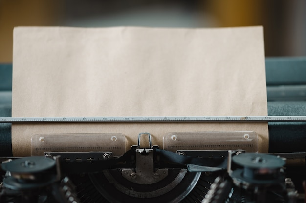 Vintage-schreibmaschine mit eingelegtem braunem papierblatt