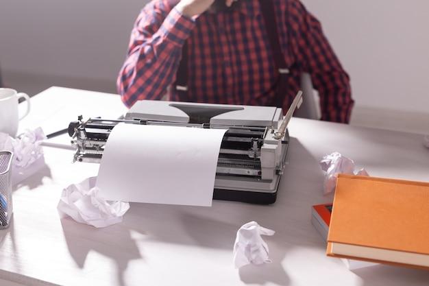 Vintage, schriftsteller und hipster-konzept - junger stilvoller schriftsteller, der an schreibmaschine arbeitet