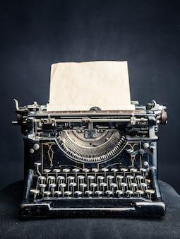 Vintage schwarze schreibmaschine mit eingelegtem papierblatt