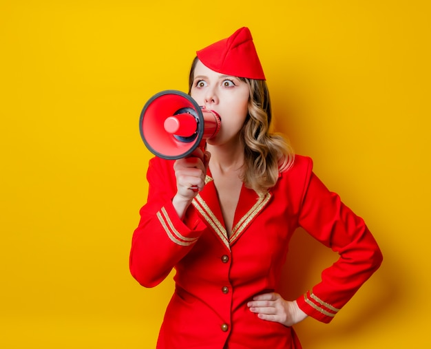 Vintage stewardess in roter uniform mit megaphon
