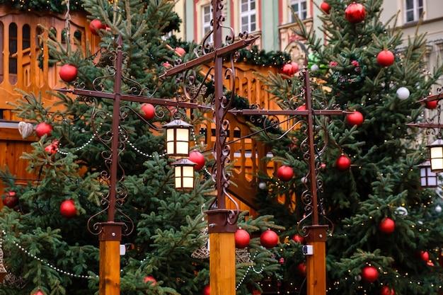 Vintage straßenlaternen und rote weihnachtskugeln mit led-girlanden auf verzierten neujahrsbäumen
