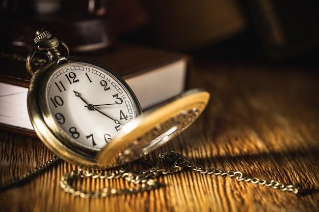 Vintage taschenuhr auf holzoberfläche gegen ein altes buch