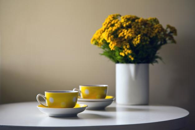 Vintage teeset - zwei gelbe gepunktete retro-tassen und gelbe chrysanthemenblüten auf weißem tisch.