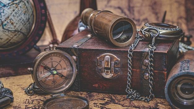Vintage teleskop, kompass und alte sammlung auf schatzkiste