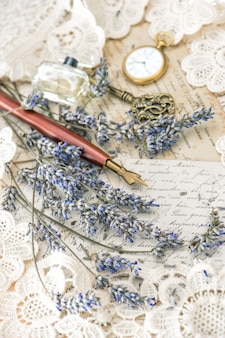 Vintage tintenstift, schlüssel, parfüm, taschenuhr, lavendelblüten und alte liebesbriefe. getöntes bild im retro-stil