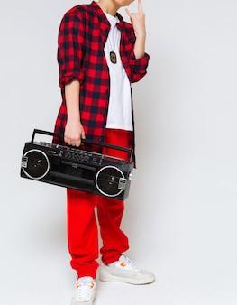 Vintage tonbandgerät in den händen eines jungen. der junge trägt eine rote hose, ein kariertes hemd und ein weißes t-shirt. studioaufnahme. vertikales foto