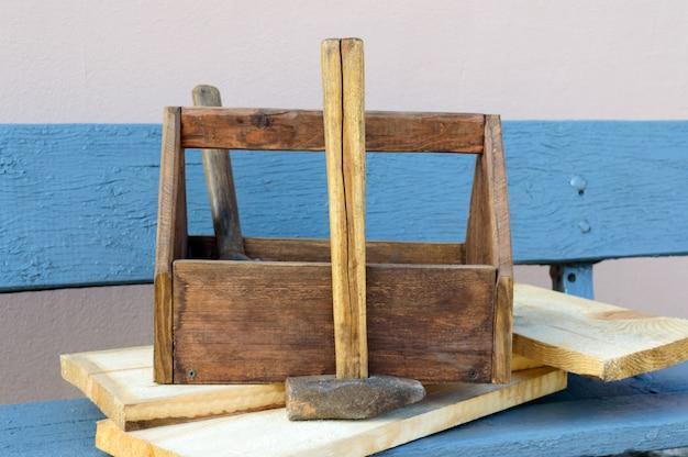Vintage toolbox mit werkzeugen. alte holzkiste mit bauwerkzeugen, bretter zur reparatur auf einer holzbank. tischler-werkzeugkasten. alte arbeitsgeräte.