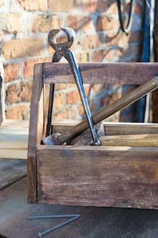 Vintage toolbox mit werkzeugen. alte holzkiste mit bauwerkzeugen, bretter zur reparatur. tischler-werkzeugkasten. alte arbeitsgeräte.