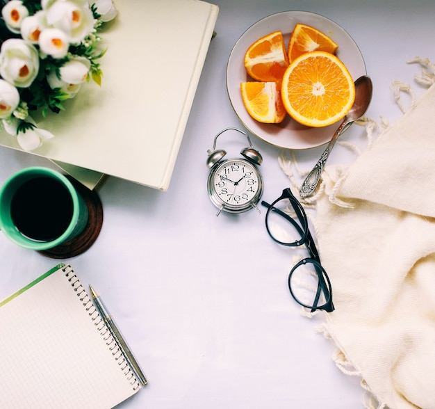 Vintage uhr auf einem schreibtisch mit einer tasse heißen kaffee und frischem obst