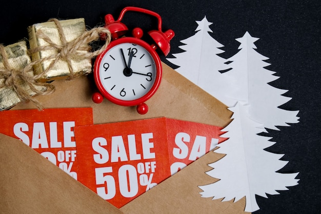 Vintage uhr mit geschenkboxen auf roten aufklebern mit rabatten mit einem handwerksumschlag und papierweihnachtsbäumen