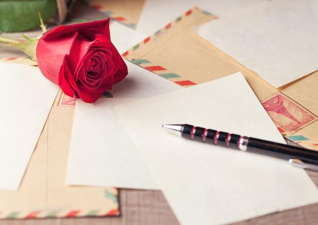 Vintage umschläge, rote rose und blätter papier auf dem tisch verstreut