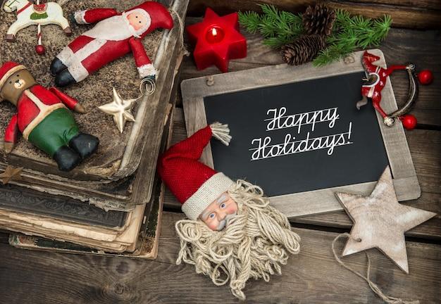 Vintage weihnachtsdekoration mit antiken kugeln und spielzeug auf holzuntergrund. tafel mit beispieltext frohe feiertage! sentimentales nostalgisches bild im retro-stil. dunkles design, selektiver fokus