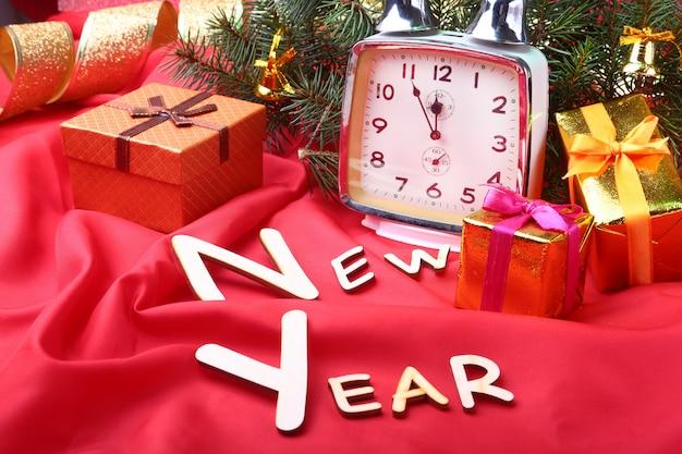 Vintage weihnachtsuhr. neujahrsdekoration mit geschenkboxen, weihnachtskugeln und baum. feier-konzept für neujahr.