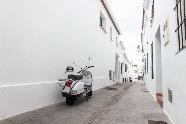 Vintage weißer roller steht auf einer straße nahe einer wand. schöne schmale straße mit weißen alten gebäuden in spanien.