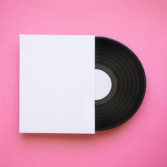 Vinyl-mock-up mit papier auf rosa hintergrund