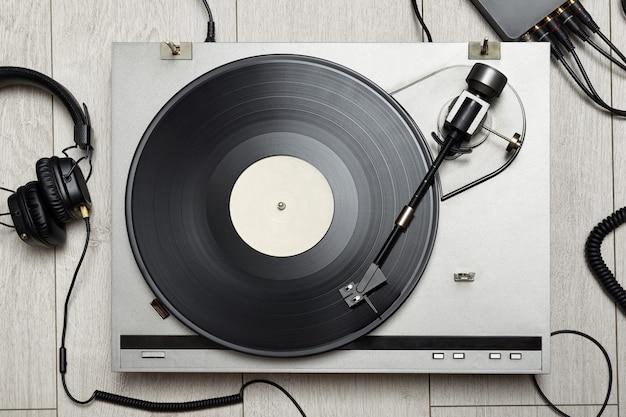 Vinyl-player mit longplay- oder lp-schallplatte und altmodischen kopfhörern. ansicht von oben.