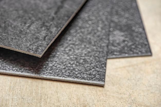 Vinyl-pvc-boden die textur des vinyl-bodens besteht aus schwarzen vinylproben, die schwarze pvc-fliesen auf...