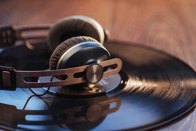 Vinylaufzeichnung und kopfhörer über holztisch. audio-enthusiasten, musikliebhaber oder professionelle discjockey-ausrüstung.