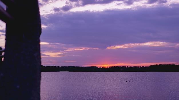 Violett-violetter sonnenuntergang, schwarze meeresoberfläche unter lila himmel