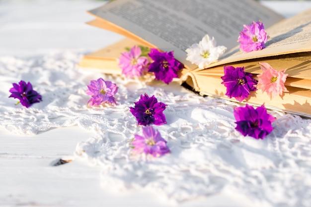 Violette blumen gelichrysum auf einem buch. durchbrochene gestrickte tischdecke auf einem alten holztisch. abend im dorf. sonnenuntergang im freien, batanica, schöne blumen im glas.
