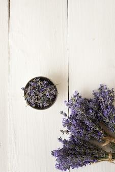 Violette blumensträuße aus duftenden lavendelblüten mit einer piala auf weiß. flach liegen