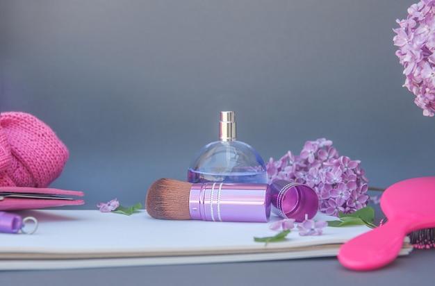 Violette kreisparfümflasche und make-up-pinsel mit verschiedenen blumen, horizontaler platz für text