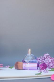 Violette kreisparfümflasche und make-up-pinsel mit verschiedenen blumen, vertikaler platz für text