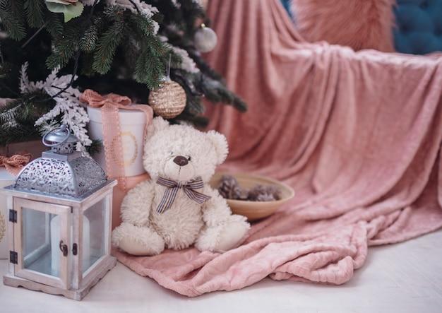 Violette laterne und großer teddybär stehen unter dem weihnachtsbaum vor einem gemütlichen rosa stuhl