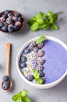 Violette magische smoothieschüssel überstiegen mit blaubeeren, brombeeren, kokosnussflocken und samen
