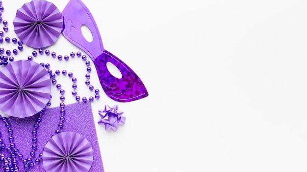 Violette maske und dekorationen auf weißem hintergrund des kopierraums