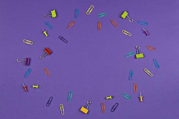 Violette oberfläche mit bunten briefpapiereinzelteilen