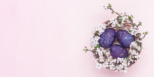 Violette ostereier in einem korb mit blumen auf einem rosa hintergrund.