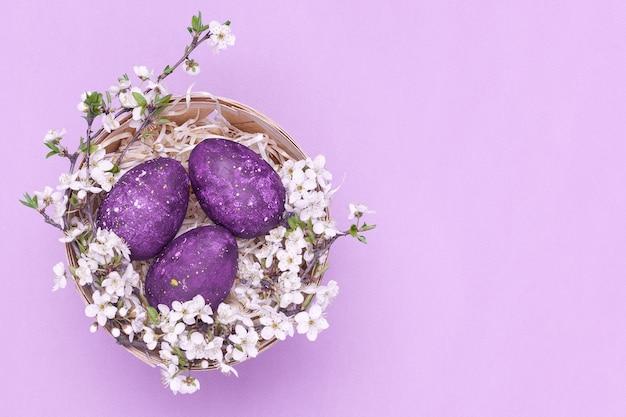 Violette ostereier in einem korb mit blumen auf einem violetten hintergrund.