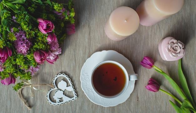 Violette tulpen, rosa duftkerzen und eine tasse tee