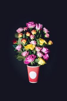 Violette und gelbe rosen setzen in rote papiertasse