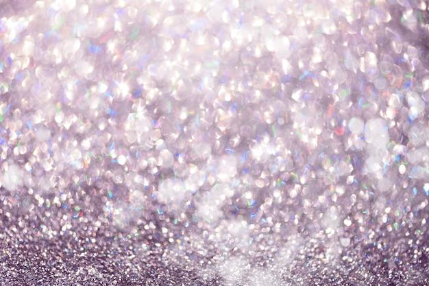 Violette und purpurrote abstrakte bokeh lichter. glänzender funkelnhintergrund mit kopienraum. neues jahr und weihnachtskonzept. funkelnde grußkarte