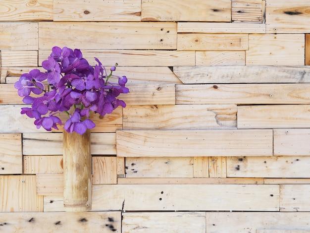 Violette wanda-orchidee im bambusvase, der an der hölzernen plankenwand hängt.