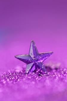 Violetter stern auf einem lila funkelnhintergrund auf einem undeutlichen purpurroten hintergrund