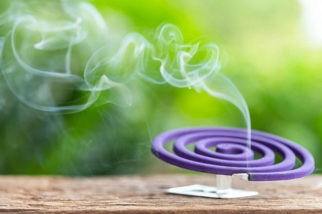Violettes moskitoabwehrmittel auf holztisch mit grünem unschärfelichtraumhintergrund