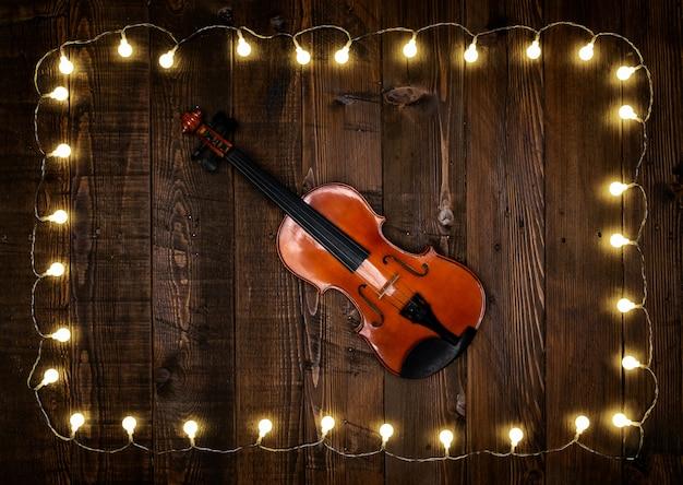 Violine auf hölzernem hintergrund mit glühlampen