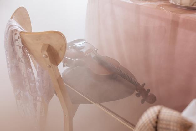 Violine liegt auf einem stuhl in einem bankettsaal im nebel