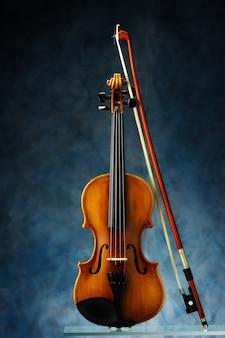 Violine mit bogen auf blauer wand.